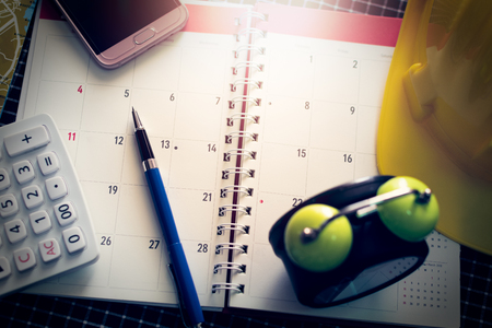 Notebook calendar with pen, mobilephone, calculator, clock and construction helmet on the desk under light.
