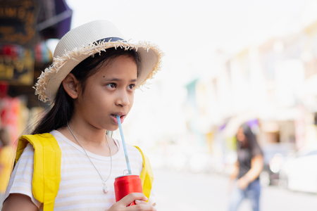 Cute girl traveler is drinking cold soft drink in thalang road during summer time, Phuket, Thailand.