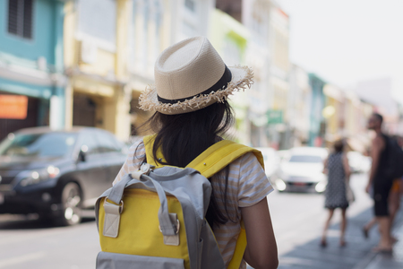 Young girl Traveler with backpack standing in old town among chino portuguese style building in thalang road, Phuket, Thailand. Travel concept.