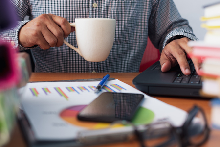 Man is drinking a cup of coffee and working with stack of documents on office desk, Businessman is analyzing marketing with statistics chart, Business and Office life concept.