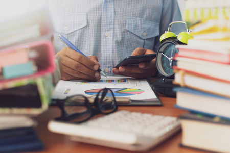 Man is using mobile phone and working with stack of documents on office desk, Businessman is analyzing marketing with statistics chart, Business and Office life concept.