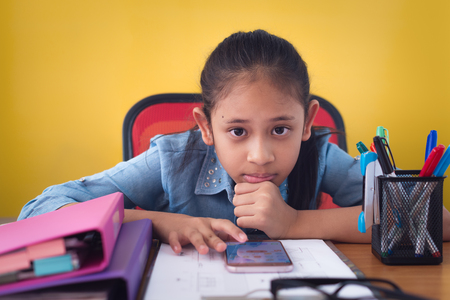 Cute girl using mobile phone on the desk isolated yellow background. Concept of achievement.