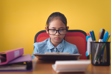 Cute girl wearing glasses working with document on the desk isolated on yellow background, Education concept. Stock Photo