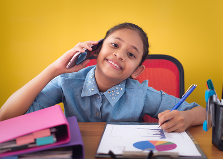 Cute girl using mobile phone and smiling on the desk isolated yellow background. Concept of achievement. Stock Photo