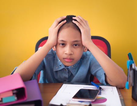 Cute girl holding her head upset by hard work. Stressed girl troubled with problem on working desk isolated yellow background. Stock Photo