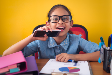 Cute girl wearing glasses smiling with happiness isolated on yellow background. Business girl overjoyed about successfully completed project on the desk. Concept of achievement.