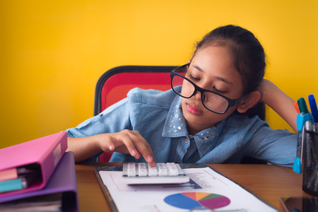 Cute girl wearing glasses is boring with hard work on the desk, Business girl is sleepy while working isolated on yellow background, Education concept. Stock Photo