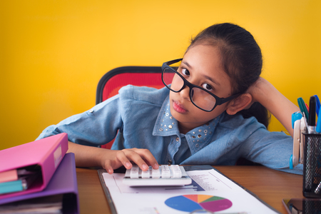 Cute girl wearing glasses is boring with hard work on the desk isolated on yellow background, Education concept.