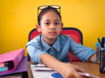 Cute girl working on the desk with document isolated yellow background. Concept of achievement.