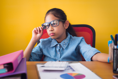 Cute girl wearing glasses using the idea of planning work on the desk with document isolated yellow background, Education concept.