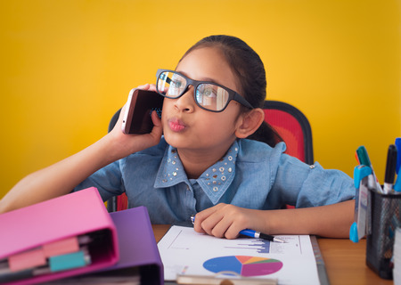 Cute girl thinking and talking on the phone at the desk isolated yellow background, Education and communication concept. Stock Photo