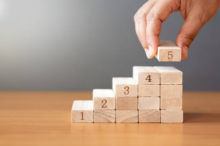 Women hand putting a wooden block on top and arranging wooden blocks stacking on wooden table in the shape of a staircase, Business concept for growth success process. Stock fotó