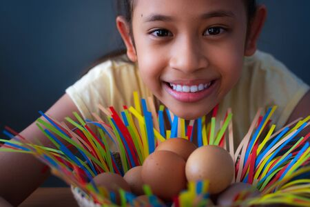 Close up cute asian girl smiling with chicken eggs in a basket, Easter concept.