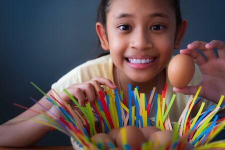 Close up cute asian girl smiling and holding a chicken egg, Easter concept. Imagens