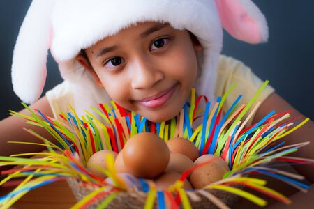 Happy easter! Close up cute girl wearing rabbit hat with chicken eggs in a basket, Easter holiday concept. Imagens