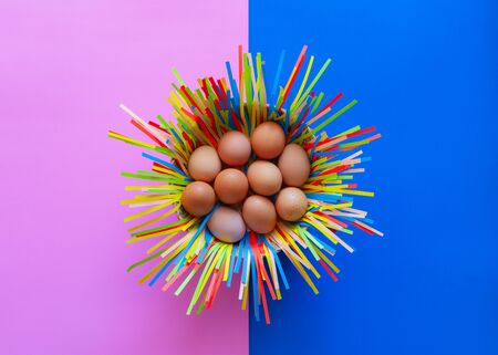 Chicken eggs in a basket on pink and blue paper background, Easter eggs concept.