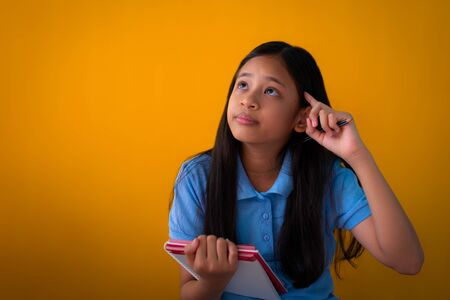 Portrait of asian cute girl holding a book and thinking isolated orange background, Long hair girl with blue shirt.