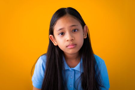 Portrait of serious asian cute girl isolated orange background, Long hair girl with blue shirt. Imagens