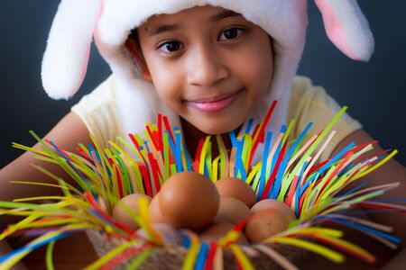Happy easter! Close up cute girl wearing rabbit hat with chicken eggs in a basket, Easter holiday concept. Stock Photo
