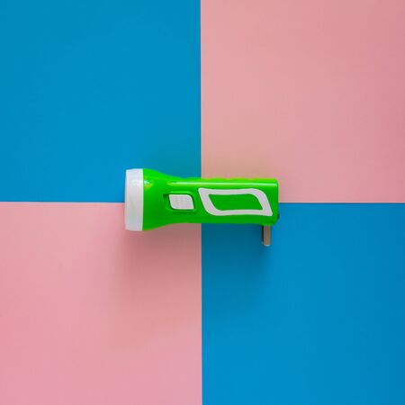 Top view green flashlight on pink and blue paper background. Imagens