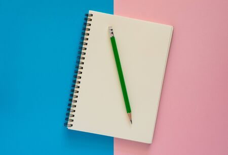 Open notebook with green pencil isolated on pink and blue paper background, Education concept. Imagens