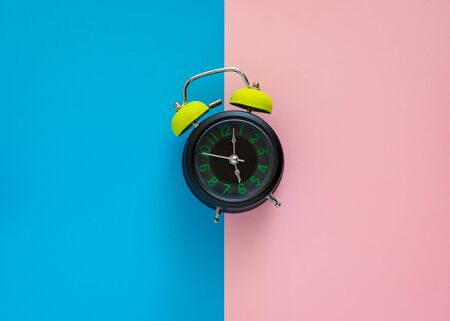 Alarm clock isolated on two tone pink and blue paper background. Imagens