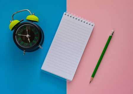 Open notebook with green pencil and alarm clock isolated on pink and blue paper background, Education concept.