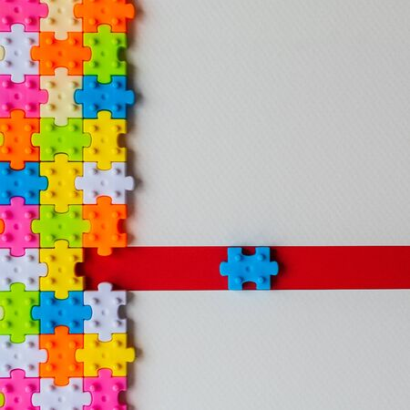 Colors plastic jigsaw puzzle on white paper background, Missing one jigsaw puzzle on red line to complete with copy space, Business strategy teamwork and problem solving concept. Reklamní fotografie