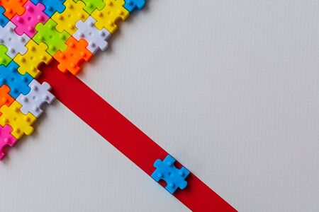 Colors plastic jigsaw puzzle on white paper background, Missing one jigsaw puzzle on red line to complete with copy space, Business strategy teamwork and problem solving concept. Imagens
