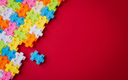 Colors plastic jigsaw puzzle on red paper background, Missing one jigsaw puzzle to complete with copy space, Business strategy teamwork and problem solving concept.