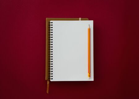 Blank white notepad with pencil isolated on red paper background, Education inspiration concept. Reklamní fotografie