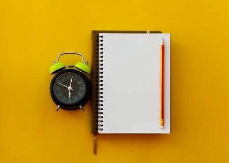 Blank white notepad with pencil and alarm clock isolated on yellow background, Education inspiration concept. Imagens