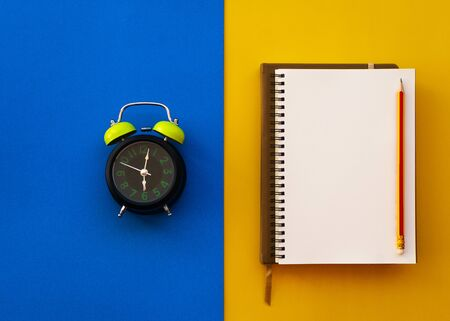 Blank white notepad with pencil and alarm clock isolated on two tone yellow and blue background, Education inspiration concept.