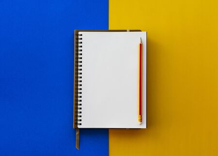 Blank white notepad with pencil isolated on two tone yellow and blue background, Education inspiration concept.