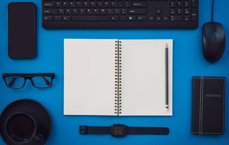 Blank white notepad with black office and personal accessories isolated on blue background, Business motivation and inspiration concepts. Reklamní fotografie