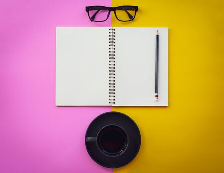 Blank white notepad with black coffee cup, pencil and glasses on two tone pink and yellow background. Business inspiration concepts.