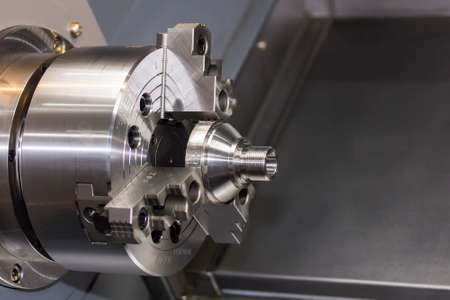 Close up spindle chuck and product part set on high precision Cnc industrial lathe turning machine