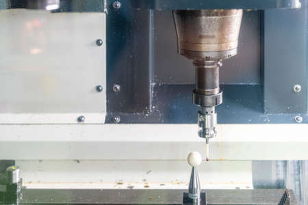 close up automatic coordinate measuring probe during calibrate with standard ball for inspection dimension work piece or product on table of machining center for manufacturing process in industrial Stock Photo