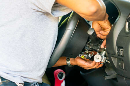 close up hand of technician during repair key or switch engine start of sedan car