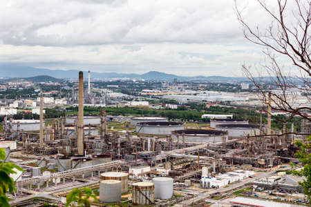 View of oil refinery and petrochemical plant with background cloudy sky and mountain in evening day at thailand