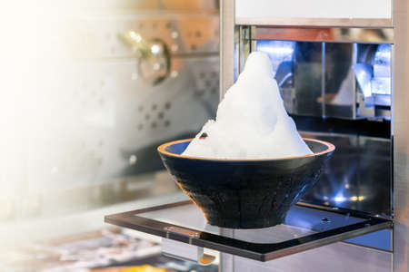 Close up ice flake or snowflake made from modern and automatic bingsu machine in bowl (asian or korean dessert) with copy space