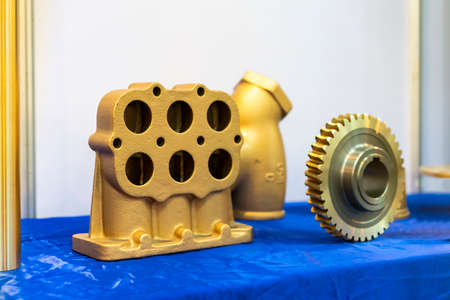 Industrial casting and machining parts gas - air intake manifold and gear or sprocket for automotive or machine on blue table