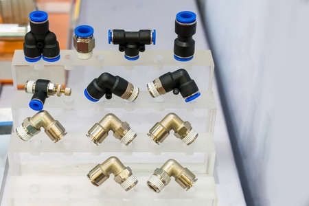 many kind of metal and plastic quick coupling or fittings equipment connector for air or liquid on shelf Stock Photo