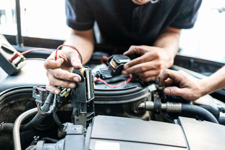 People or mechanic car repair during investigate cause of problem (electric system check) or working on automobile gasoline or diesel engine at garage Stock Photo
