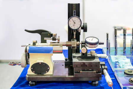 Metal bolt and nut with dial gauge during setup on modern thread checking instrument for industrial on blue table Stock Photo