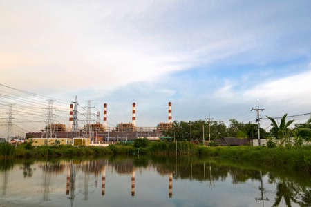 Natural gas electric power plant with smokestack and many pole in chonburi thailand with water reflection and beautiful sky near evening Banco de Imagens