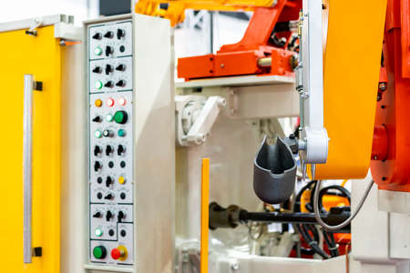 close up ladle and mechanical arm of high pressure aluminum die cast machine and other detail such as control panel etc for automobile or vehicle part manufacturing at factory or foundry