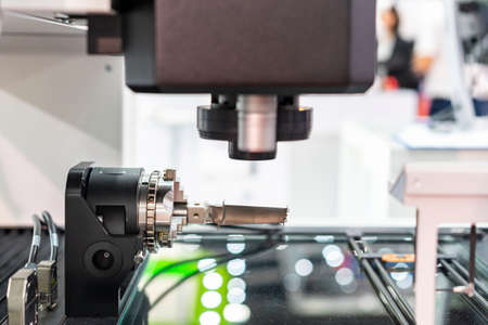 production parts or sample from manufacturing process during hold by rotary chuck on table of high technology & precision automatic measuring machine for multi inspection dimension shape appearance Stock Photo
