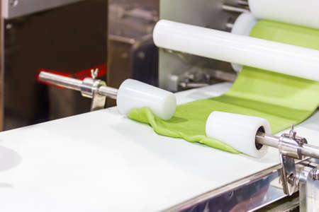 close up cylindrical die and rolled dough on belt conveyor of automatic food making machine for chinese or asian food (steamed stuffed buns) by high technology industrial food manufacturing