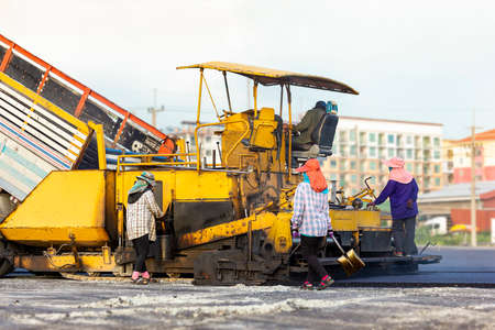 Many workers with equipment helped to build or paver the road with asphalt compactor finisher machine in the afternoon